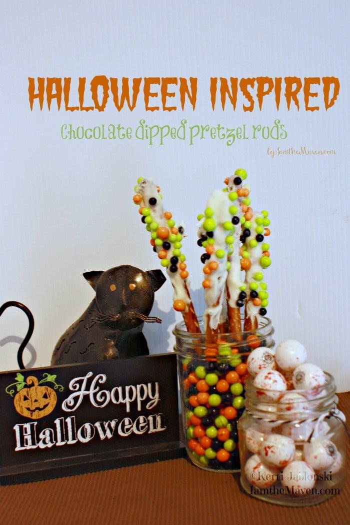 halloween candy display with halloween sign, chocolate dipped pretzel rods and candy eyeballs