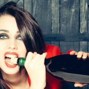 Girl opening wine with teeth