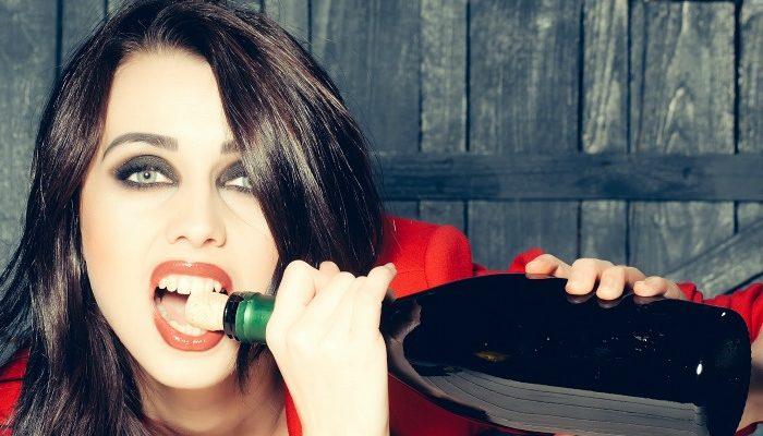 Girl opening wine with teeth