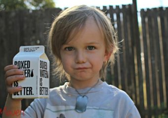 Little boy holding boxed water