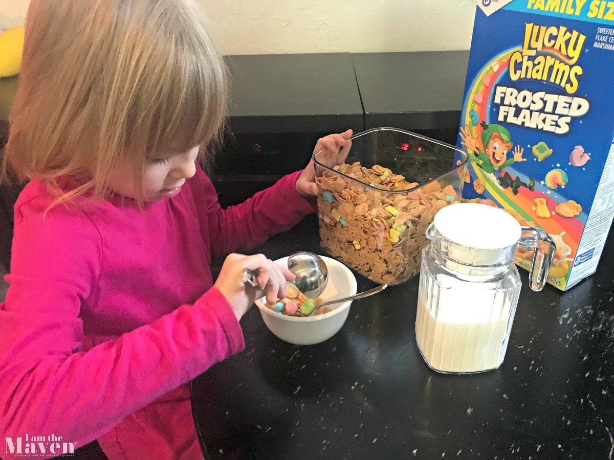 little girl putting cereal in a bowl