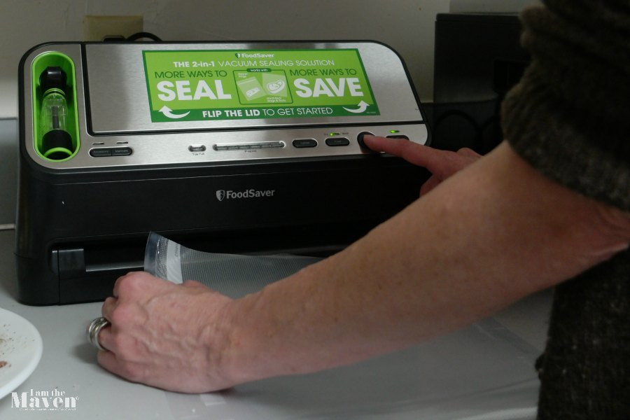 Press the seal button on your FoodSaver® V4440. With two hands, slowly insert open end of bag, curl down, into Vacuum Channel until clamp motor starts.