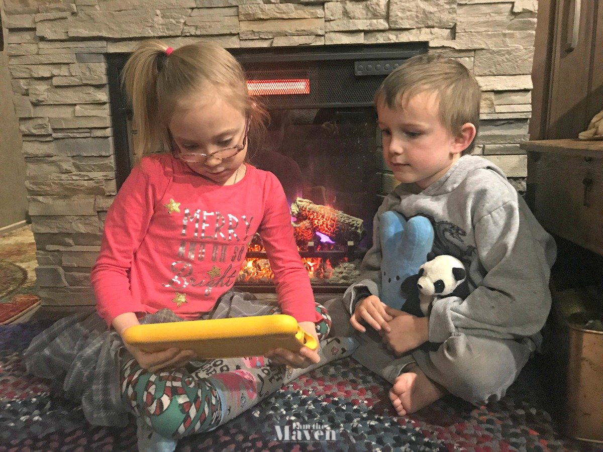 kids looking at kindle fire by fireplace