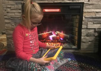 little girl reading a tablet by the fire