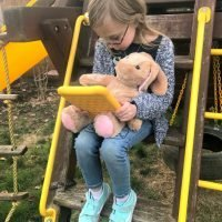 ittle girl with toy bunny reading on fire kids edition