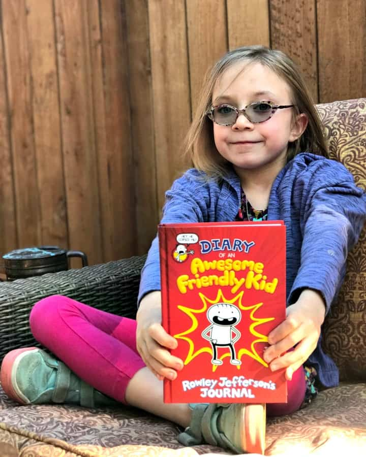 girl on couch with diary of an awesome friendly kid book