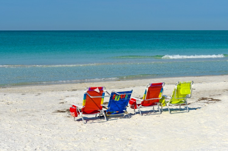 Four Empty Bright Color Beach Chairs on the Beach