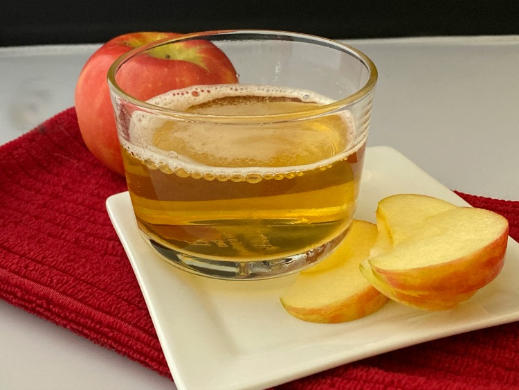 glass of apple cider with apple slices