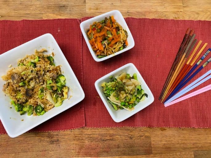 easy at home family date night - chinese food in white bowls on a red placemat