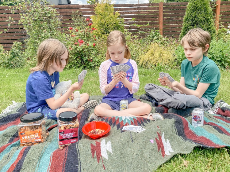 kids playing cards sitting on a picnic blanket