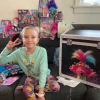 blonde girl with trolls toys and gift box
