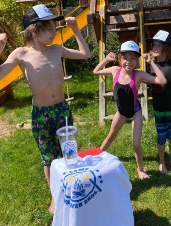 kids in bathing suits by a swingset showing off their muscles