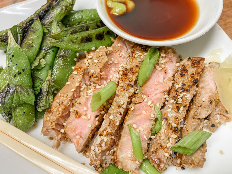 sesame crusted tuna and grilled snap peas with soy sauce on a white plate