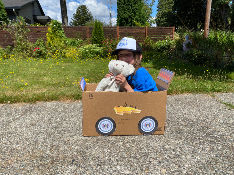 little boy in a cardboard box car