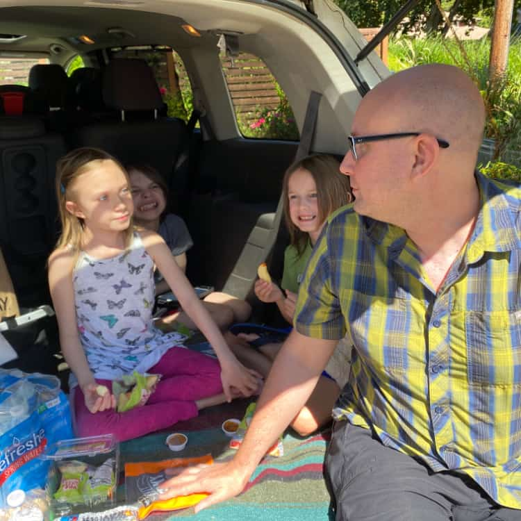 dad with kids having a picnic in a van