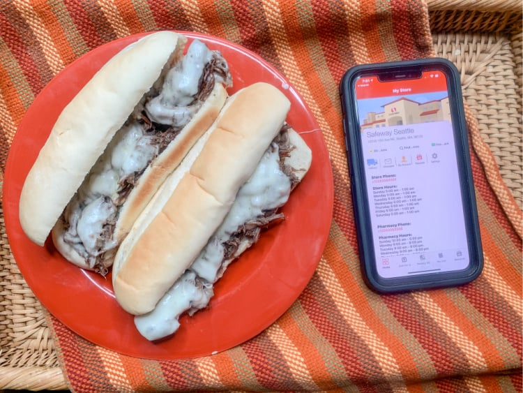cheesesteaks on a red plate with phone showing safeway app