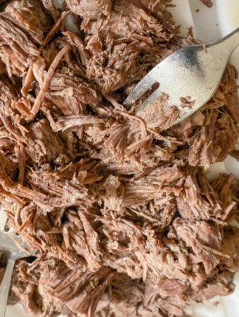 shredded beef on cutting board