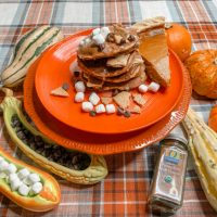fall goards, small pumpkins, a stack of pancakes and a slice of pumpkin pie on a plate, all on a plaid table cloth