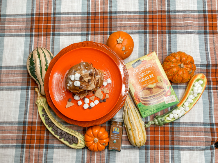 stack of pumpkin pancakes on an orange plate on a plaid table cloth with a box of pancake mix and decorative gourds