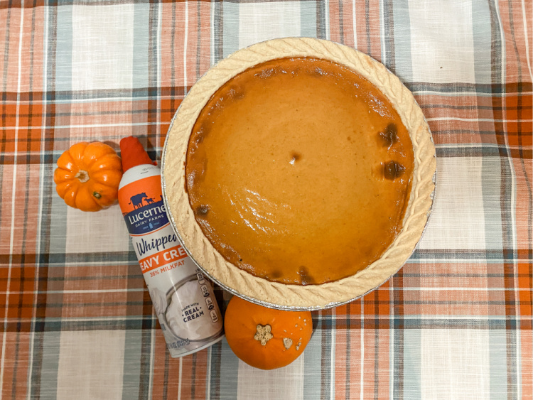 pumpkin pie with a can of whipped cream and two small pumpkins on a plaid table cloth