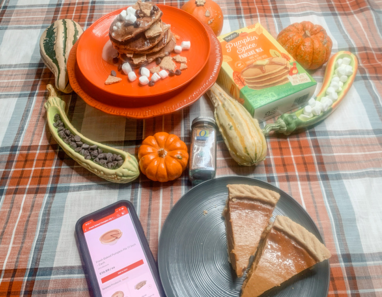 stack of pumpkin pancakes on an orange plate, two slices of pie on a grey plate on a plaid table cloth with a box of pancake mix and decorative gourds