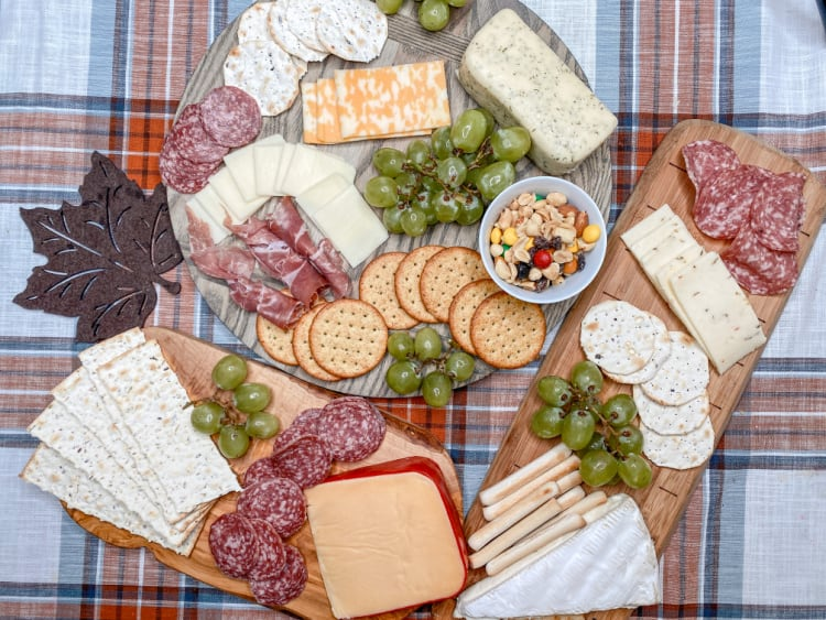 cutting boards with meats, cheeses and crackers