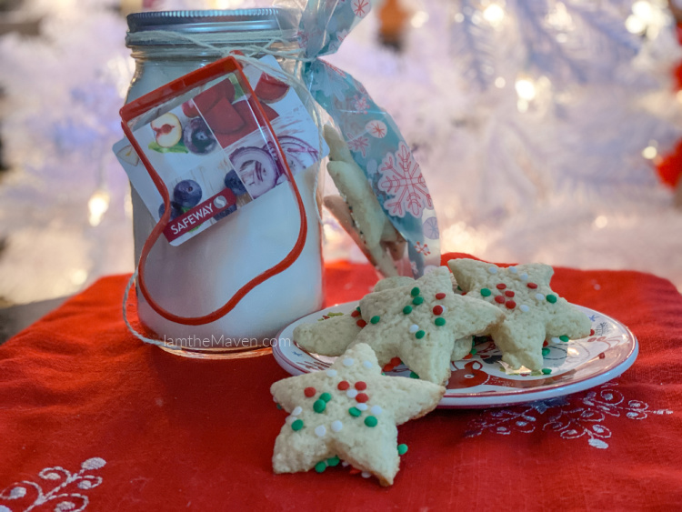 cookie mix in a jar, with a plate of cookies, on a red table cloth in front of a white christmas tree