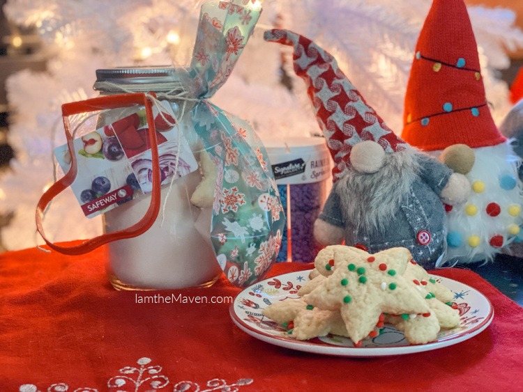 jar of cookie mix, cookies on a plate, two gnomes on a red table cloth in front of a white christmas tree