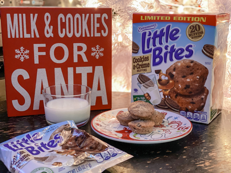 glass of milk, milk and cookies sign, muffins on a plate and little bites packaging, all in front of white christmas tree