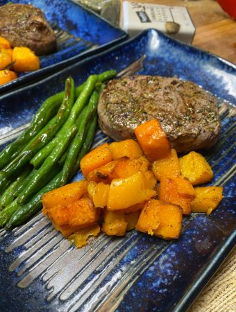 filet mignon and roasted vegetables on a blue plate
