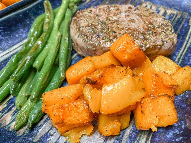 filet mignon, butternut squash and green beans on a blue plate