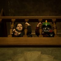 little boy and creepy toy peeking through railing