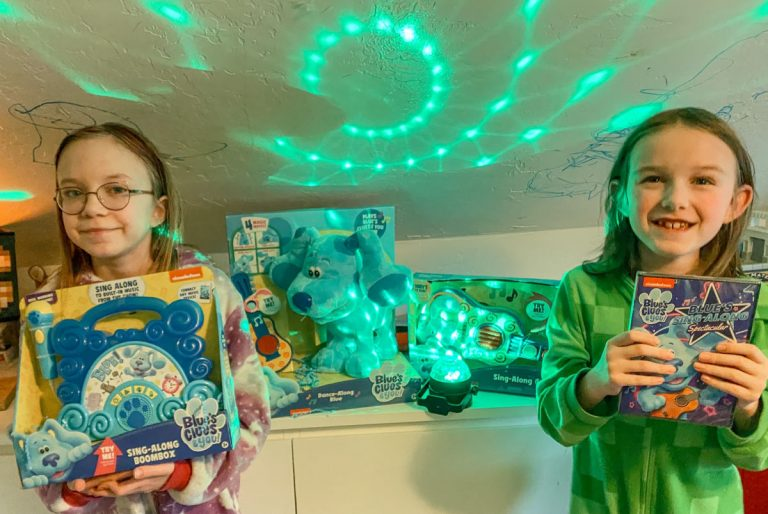two children wearing pajamas posing with blues clues toys