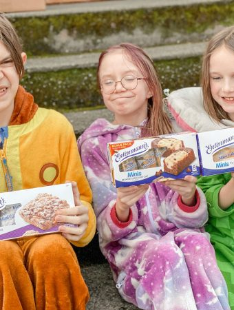 3 kids sitting on steps holding boxes of entenmann's mini snack cakes