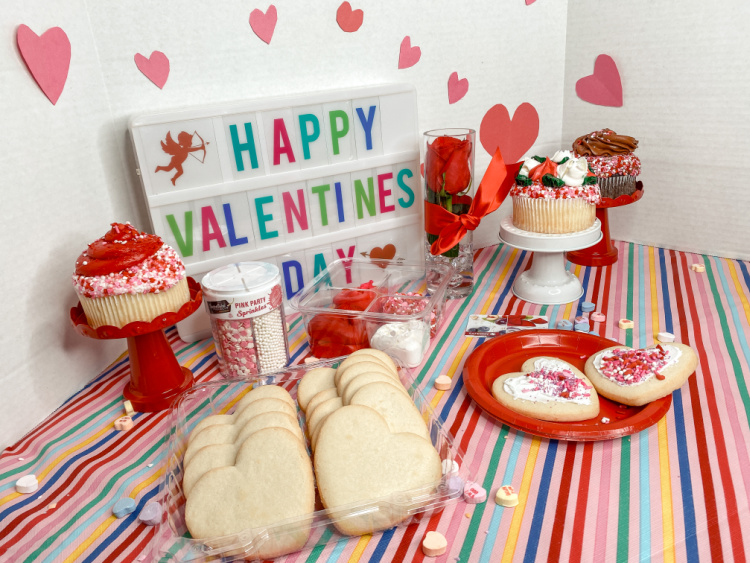 valentines day party tablescape with a sign, cookies and cupcakes on a striped tablecloth