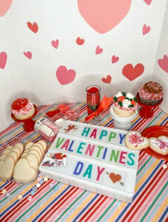 valentine's day sign with colorful letters, unfrosted heart shaped cookies, decorated cupcakes on a striped tablecloth