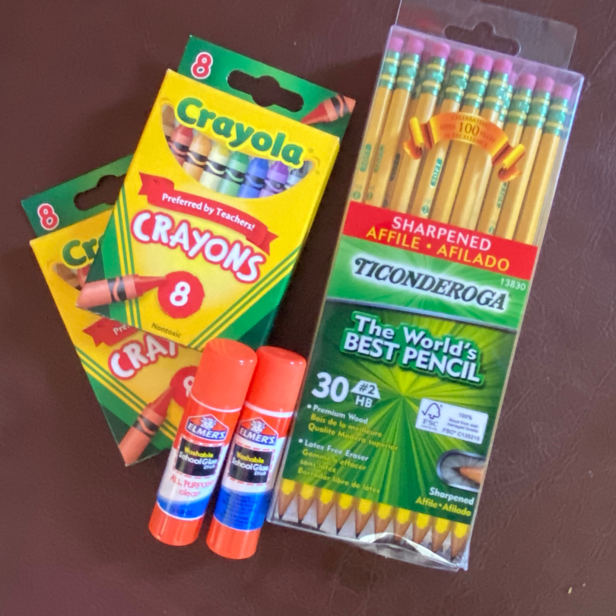 two boxes of crayons, two glue sticks and a pack of pencils
